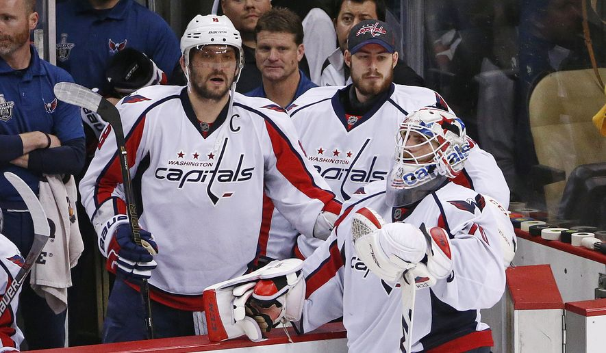 Washington Capitals goalie Braden Holtby (70) stands with teammates Alex Ovechkin (8) and Philipp Grubauer, center, as the Pittsburgh Penguins celebrate a 4-3 overtime win during Game 6 of the NHL hockey Stanley Cup Eastern Conference semifinals, Tuesday, May 10, 2016 in Pittsburgh. (AP Photo/Gene J. Puskar)