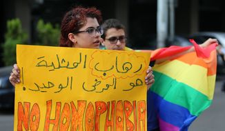 """Supporters of the LGBT (Lesbian, Gay, Bisexual, and Transgender) community attend a sit-in to protest the ongoing criminalization of homosexuality and arbitrary arrests, in front of Hobeich Police Station, where protesters say four men are being held for homosexuality, in Beirut, Lebanon, Sunday, May 15, 2016. Arabic reads, """"The only disease is homophobia."""" (AP Photo/Hussein Malla) ** FILE **"""