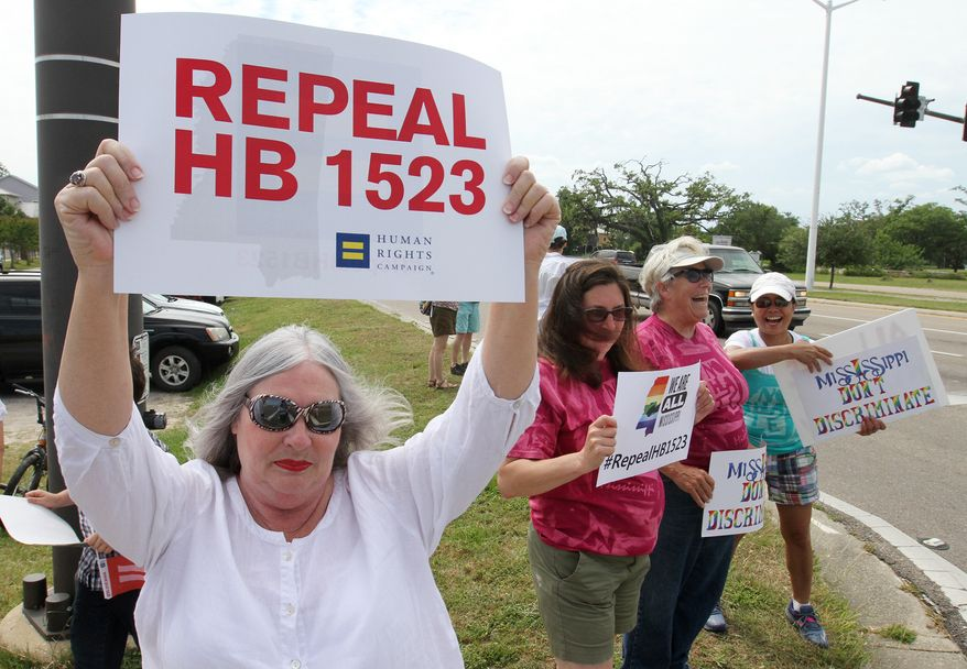 Micky Evans holds a sign during a rally in Bay St. Louis, Miss., Sunday May 15, 2016. The event brought together people from several organizations to protest a law they say discriminates against people who are transgender known as HB 1523. People were also there to protest the state flag. (John Fitzhugh/The Sun Herald via AP) LOCAL TELEVISION OUT; MANDATORY CREDIT: MISSISSIPPI PRESS OUT; LOCAL TELEVISION OUT WLOX, LOCAL ONLINE OUT; GULFLIVE.COM OUT
