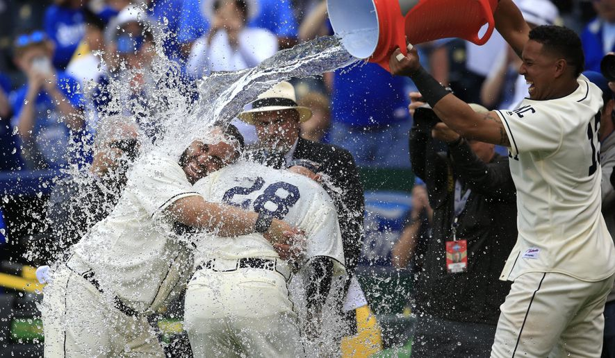 Kansas City Royals designated hitter Kendrys Morales, left, holds on to his interpreter and catching coach Pedro Grifol (28) while getting doused by teammate Salvador Perez, right, following a baseball game against the Atlanta Braves at Kauffman Stadium in Kansas City, Mo., Sunday, May 15, 2016. The Royals defeated the Braves 4-2 in 13 innings. (AP Photo/Orlin Wagner)