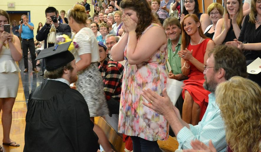 "In a Saturday, May 14, 2016 photo provided by the University of Maine at Presque Isle, University of Maine at Presque Isle's  Timothy Babine proposes to his girlfirend, Hayley Hamilton, during commencement exercises at the school. Hamilton shook her head ""yes,"" and Babine placed an engagement ring on her finger. The crowd cheered. (Rachel Rice/University of Maine at Presque Isle via AP)"