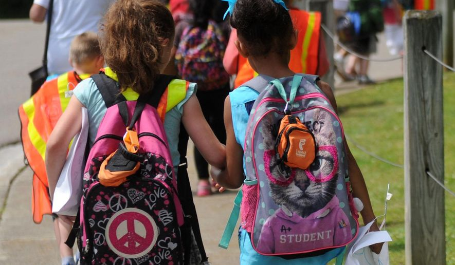 In this photo taken Wednesday, May 11, 2016, Christenberry Elementary School students take part in the Walking School Bus program in Knoxville, Tenn. The program helps children after school to walk safely to their guardians while also providing exercise. (Caitie McMekin/Knoxville News Sentinel, via AP)