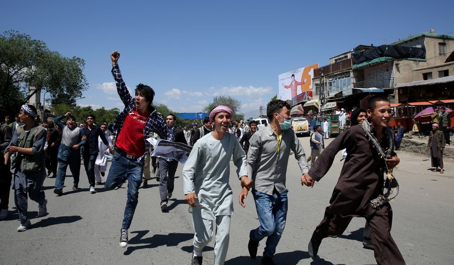 Protesters run during a massive anti-government protest in Kabul, Afghanistan, Monday, May 16, 2016. Authorities locked down Afghanistan's capital Monday as tens of thousands of members of an ethnic minority group marched through the streets to protest the proposed route of a power line. (AP Photo/Massoud Hossaini)