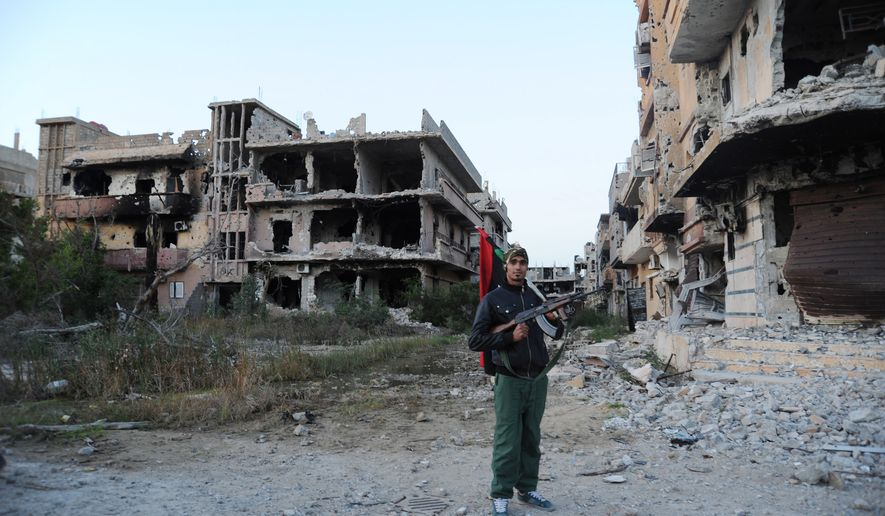 A civilian fighter holding the Libyan flag stands in front of damaged buildings in Benghazi, Libya, on Feb. 23, 2016. (Associated Press) **FILE**