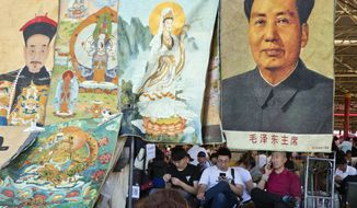 Vendors wait for customers at a curio market near a display of former Chinese leader Mao Zedong alongside images of emperors and deities in Beijing, China, Monday, May 16, 2016. (AP Photo/Ng Han Guan)