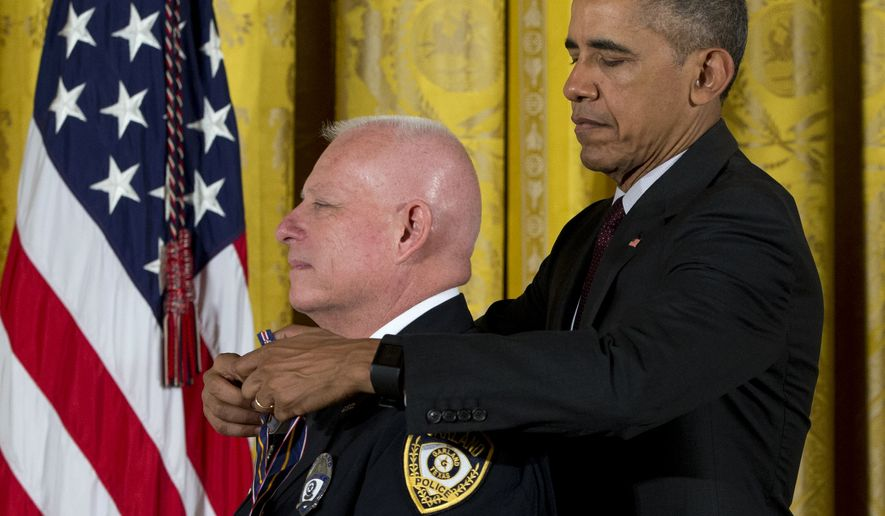 President Barack Obama presents Garland, Texas Police Department Officer Gregory Stevens with the Medal of Valor during a ceremony in the East Room of the White House in Washington, Monday, May 16, 2016. The Medal of Valor is awarded to public safety officers who have exhibited exceptional courage, regardless of personal safety, in the attempt to save or protect others from harm. (AP Photo/Carolyn Kaster)