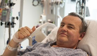In this May 13, 2016, photo provided by Massachusetts General Hospital, Thomas Manning gives a thumbs up after being asked how he was feeling following the first penis transplant in the United States, in Boston. The organ was transplanted from a deceased donor. (Sam Riley/Mass General Hospital via AP)