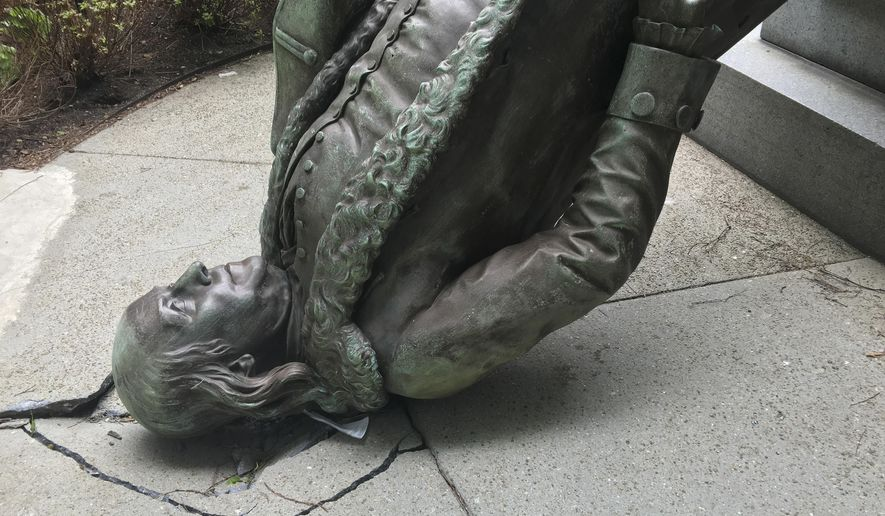 In this photo released by the City of Boston Mayor's office, a statue of Benjamin Franklin lies on the concrete outside where it landed when knocked off its pedestal outside Old City Hall in Monday, May 16, 2016, in Boston. A spokesperson for the mayor said high winds pushed a nearby tent into the statue, causing it to fall off its pedestal. (City of Boston via AP)