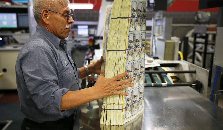 In a Wednesday, April 20, 2016 photo, Juan Reyna uses a machine that vibrates to aerate a stack of $100 notes before a digital inspection at the Bureau of Engraving and Printing in Fort Worth, Texas. This helps keep the machine from getting a paper jam during the inspection process. (Vernon Bryant/The Dallas Morning News via AP)