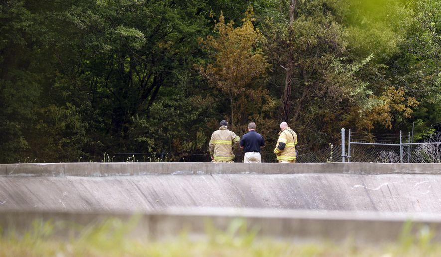 Firefighters look over the scene of a plane crash near the Tupelo Regional Airport on Colonial Estates Road, Monday morning, May 16, 2016, in Tupelo, Miss. The pilot and three passengers all died when the single-engine plane crashed in a field adjoining the Tupelo Buffalo Park & Zoo. (Thomas Wells/The Northeast Mississippi Daily Journal via AP) MANDATORY CREDIT