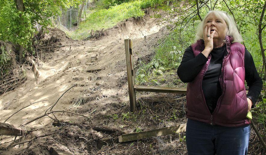 Leila Shultz looks at where a small landslide went through her backyard Monday, May 16, 2016, in Logan, Utah. (Eli Lucero/Herald Journal via AP) MANDATORY CREDIT