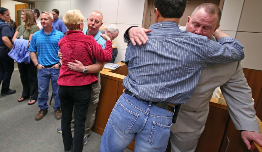 Victims' family, friends, and law enforcement, including Village Public Safety Officer Mark Haglin, right, console each other after guilty verdicts were handed down to Nathanial Kangas for two counts of murder in the first degree in Superior Court Judge Paul Lyle's courtroom at the Rabinowitz Courthouse on Monday, May 16, 2016, in Fairbanks, Alaska. A Fairbanks jury deliberated six hours before convicting Kangas, 22, in the deaths of Sgt. Scott Johnson and Trooper Gabe Rich in May 2014, the Fairbanks Daily News-Miner reported. The officers were shot at Kangas' home in the village of Tanana, about 130 miles west of Fairbanks, as they attempted to arrest Kangas' father.  (Eric Engman/Fairbanks Daily News-Miner via AP) MANDATORY CREDIT