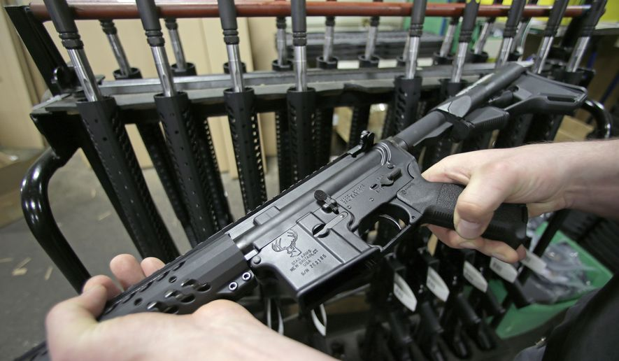 In this April 10, 2013 file photo, craftsman Veetek Witkowski holds a newly assembled AR-15 rifle at the Stag Arms company in New Britain, Conn, Wednesday, April 10, 2013. (AP Photo/Charles Krupa) ** FILE **