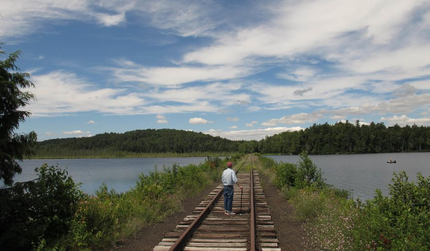 FILE - In this July 26, 2013 photo, Dick Beamish of Saranac Lake, a member of the Adirondack Recreational Trail Advocates, stands on deteriorating railroad tracks on a causeway across Lake Clear in Saranac Lake, N.Y. Gov. Andrew Cuomo has approved a plan to divide a 119-mile state-owned rail corridor through the Adirondacks to extend a scenic train route and create a new multi-use trail. (AP Photo/Mary Esch, File)