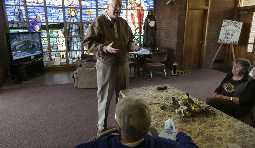 FILE -- In this Monday, May 16, 2016 file photo Jon Rogers, top, a spokesman for Friends of St. Frances Cabrini, speaks with parishioners at St. Frances X. Cabrini church, in Scituate, Mass. Now that the U.S. Supreme Court has refused to hear their last-ditch appeal, parishioners who have occupied the Roman Catholic church for 11 years in defiance of the Boston archdiocese's order to close it are vowing to create an independent church outside the Vatican's control. (AP Photo/Steven Senne, File)