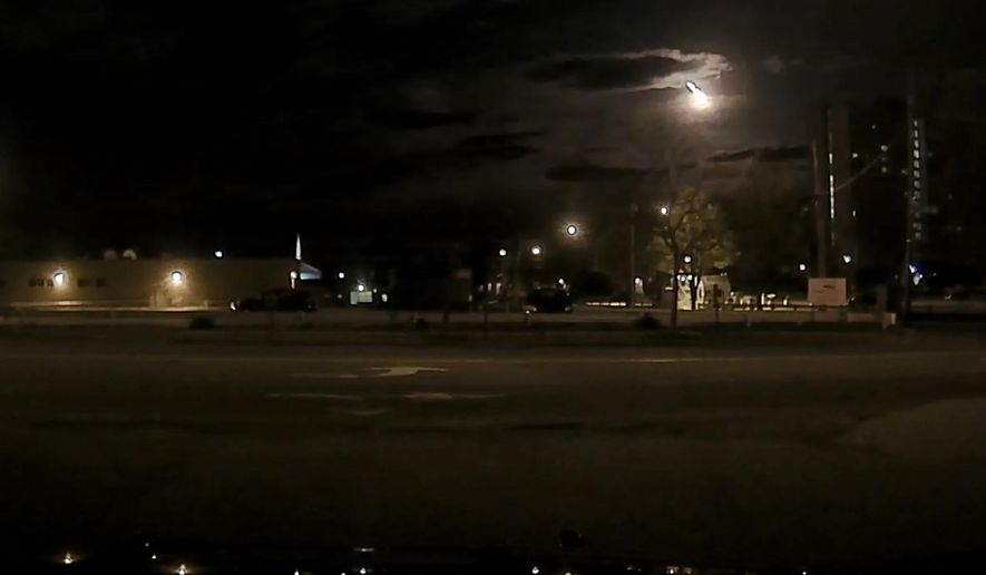 In this frame from a dashboard camera provided by the Portland Police Department, a fireball streaks across the sky early Tuesday, May 17, 2016, in Portland, Maine. The bright flash visible from several states was apparently left by a meteor burning up as it passed through the earth's atmosphere. (Portland Police Department via AP)