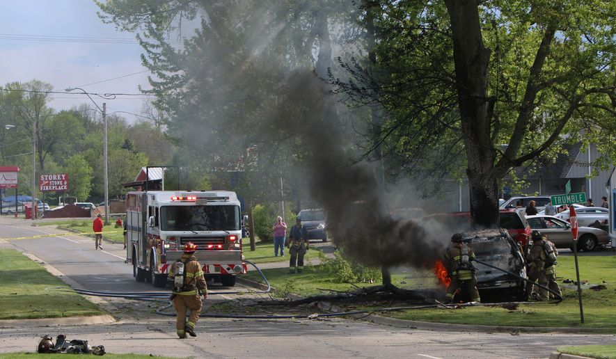 First responders work on the scene of a car crash on Francis St. in Jackson, Mich., on Monday, May 16, 2016. Authorities say a driver who sped away from a traffic stop in southern Michigan has died after losing control of the SUV he was driving and crashing into a tree. (Taylor Irby/Jackson Citizen Patriot-Mlive Media Group via AP)