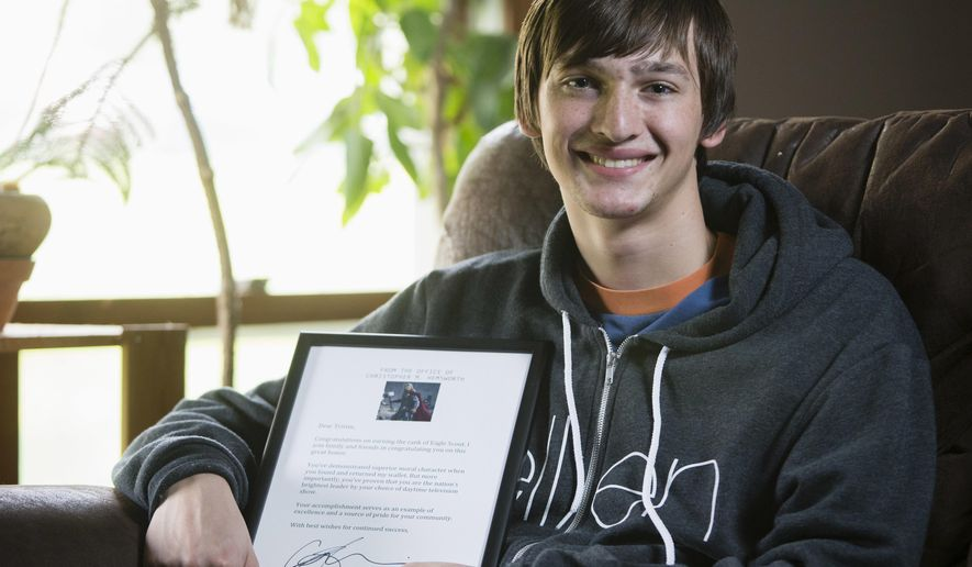 In this April 24, 2016 photo, Tristin Budzyn-Barker poses at home in Poplar Grove, Ill., with a framed letter he received from movie star Chris Hemsworth, who plays mighty Thor in the Marvel superhero movies. Budzyn-Barker became an internet sensation after he found a wallet belonging to Hemsworth at a restaurant at Los Angeles International Airport. (Max Gersh/Rockford Register Star via AP) MANDATORY CREDIT