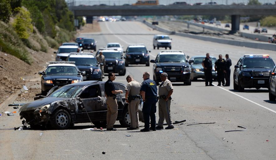 In a May 11, 2016 photo, emergency personnel investigate the scene of a shooting on westbound Highway 4 in Pittsburg, Calif. Northern California authorities are grappling with more than 20 drive-by shootings on two area freeways that have claimed six lives and injured several more. The California Highway Patrol and several police departments have created a task force to stem the roadway violence and at least one city will install security cameras to capture the shooters.  (Kristopher Skinner/Bay Area News Group via AP)
