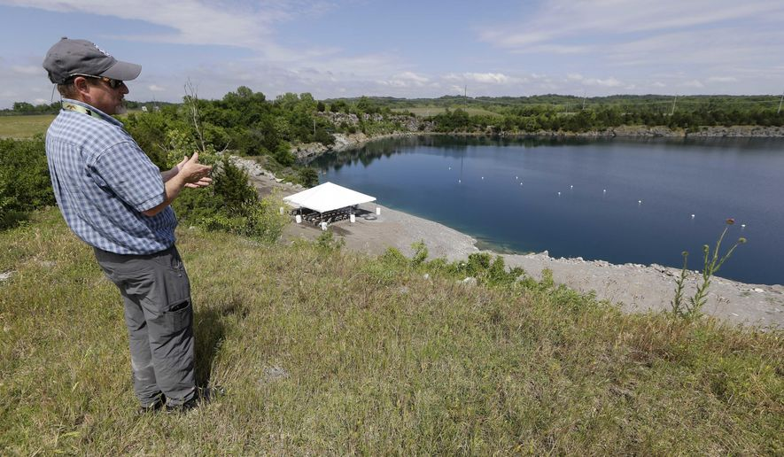 Bob Abbott, a construction inspector at the Nashville International Airport, looks over a quarry as he explains the process of a geothermal lake cooling system at the Nashville International Airport Tuesday, May 17, 2016, in Nashville, Tenn. The airport has begun using the abandoned quarry to halve its cooling costs by taking advantage of the reservoir's year-round 50-degree temperature. (AP Photo/Mark Humphrey)