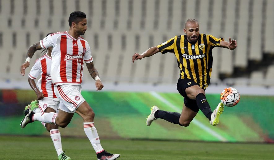Olympiakos' Manuel Da Costa, left, runs to stop AEK Athens' Rafik Djebbour as he controls the ball during the Greek Final Cup at the Olympic Stadium of Athens, on Tuesday, May 17, 2016. (AP Photo/Thanassis Stavrakis)