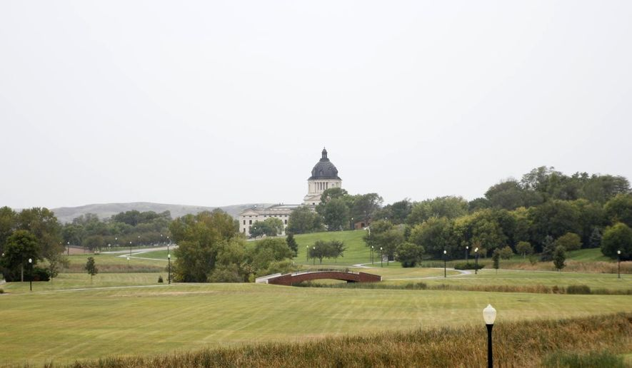 In this September 29, 2015 photo, grass on Hilger's Gulch sledding hill and in Governor's Grove seen in the background remains green, in Pierre, S.D. Crews have chemically burned off Kentucky bluegrass and are preparing to plant native grasses in parts of Hilger's Gulch park on the state Capitol grounds in Pierre. Gov. Dennis Daugaard last summer announced the initiative to replace the Kentucky bluegrass in the park to reduce maintenance, chemical use and expenses. (Nick Lowrey /Capital Journal via AP) MANDATORY CREDIT