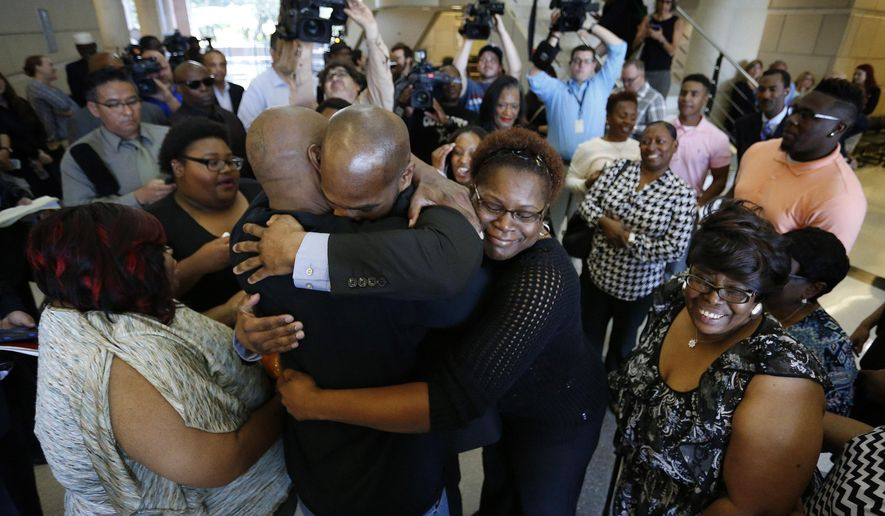 John Nolley, center facing camera, hugs his brother LaMarcus Nolley as his sister Mia Nolley hugs them following John Nolley's release from prison, at the 213th District Court, in Fort Worth Texas. Nolley, who had been found guilty of murder in 1998, was released from custody after almost 19 years behind bars due to new evidence. Nolley's mother Alice Samuel stands at right. (Paul Moseley /Star-Telegram via AP)  MAGS OUT; (FORT WORTH WEEKLY, 360 WEST); INTERNET OUT; MANDATORY CREDIT