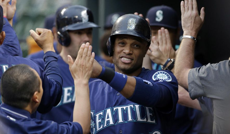 Seattle Mariners' Robinson Cano high-fives teammates in the dugout after scoring on a single by Nelson Cruz in the first inning of a baseball game against the Baltimore Orioles in Baltimore, Tuesday, May 17, 2016. (AP Photo/Patrick Semansky)