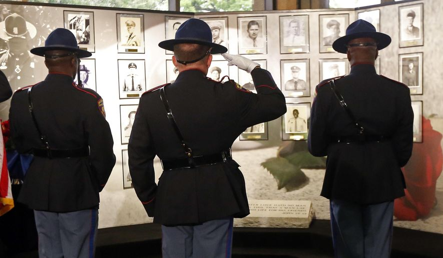A Mississippi Highway Patrol honor guard stands at attention in front of the Mississippi Department of Public Safety memorial wall at headquarters in Jackson, Miss., during the 2016 Fallen Officers Memorial Service, Tuesday, May 17, 2016. Gov. Phil Bryant, a former sheriff's deputy, addressed the survivors, relatives and friends of those state highway patrolmen and members of the Mississippi Bureau of Narcotics who have been killed in the line of duty. Law enforcement departments and agencies statewide are holding similar memorial ceremonies to honor those local lawmen who were killed in the line of duty. (AP Photo/Rogelio V. Solis)