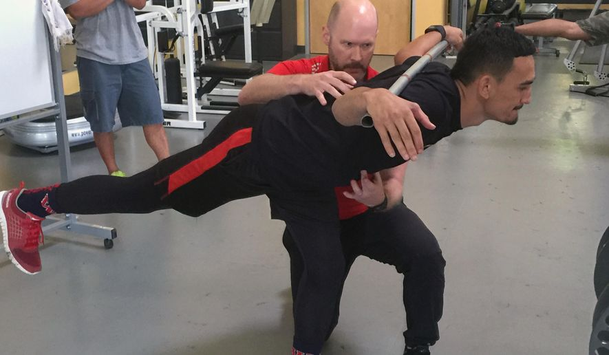 This March 31, 2016 photo provided by EXOS shows coach John Stemmerman, at rear in red shirt, and UFC fighter Max Halloway at the EXOS training facility in Phoenix, Ariz. UFC fighters are among the most fit athletes in the world and are used to pushing themselves through mental and physical pain. Even for them, a week of training at an EXOS training facility was an eye-opening experience. (Michael Cooper/EXOS via AP)