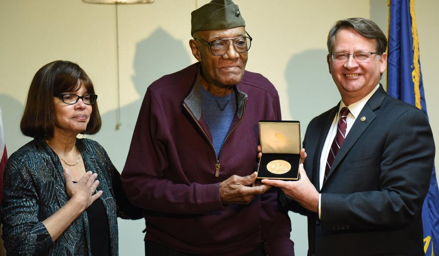U.S. Senator Gary Peters presents Montford Point Marine John Willie Jordan, 90 of Farmington Hills, Mich.,a Congressional Gold Medal for his service during WWII Monday, May 16, 2016, beside his daughter Beverly Jordan-Murphy,  of Connecticut,at American Legion Post 346 in Farmington, Mich. Jordan was one of first African Americans to serve in the U.S. Marines Corps. (Tanya Moutzalias/The Ann Arbor News-MLive.com via AP)