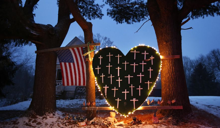 In this Dec. 14, 2013 file photo, a makeshift memorial with crosses for the victims of the Sandy Hook Elementary School shooting massacre stands outside a home in Newtown, Conn., on the one-year anniversary of the shootings. With sweeping views of Newtown's rolling hills, a field at the town's highest point emerged early on as the first choice for planners of a permanent memorial to honor the 26 people killed at Sandy Hook Elementary School. Open space advocates, however, objected to construction on the pristine area known as the High Meadow. As more community members have spoken out, the planning commission, which includes parents of the some of the massacre victims, agreed recently to go back and consider other options. (AP Photo/Robert F. Bukaty, File)