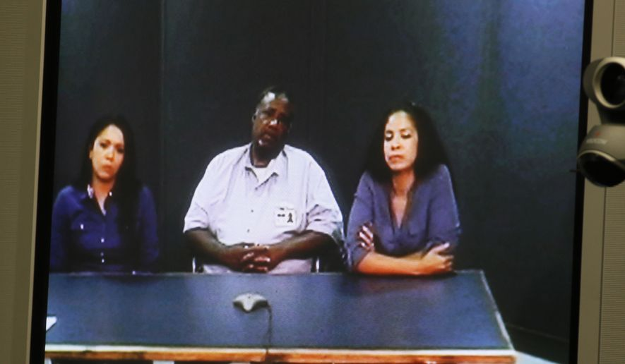 Larry Yarbrough, center, is pictured on a video screen with his daughters, Latasha Yarbrough Miller, left, and LaDonna Garrett, right, during a video conference parole hearing in Oklahoma City, Tuesday, May 17, 2016. Yarbrough, a 66-year-old Oklahoma inmate serving life in prison for possessing an ounce of cocaine, was denied parole, months after the governor modified his sentence that allowed for an option to offer him an early release. (AP Photo/Sue Ogrocki)