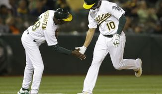Oakland Athletics' Marcus Semien, right, is congratulated by third base coach Ron Washington after hitting a home run off Texas Rangers' Luke Jackson in the seventh inning of a baseball game Monday, May 16, 2016, in Oakland, Calif. (AP Photo/Ben Margot)