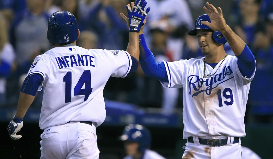 Kansas City Royals' Omar Infante (14) and Cheslor Cuthbert (19) celebrate after scoring on a single by teammate Paulo Orlando during the fourth inning of a baseball game against the Boston Red Sox at Kauffman Stadium in Kansas City, Mo., Tuesday, May 17, 2016. (AP Photo/Orlin Wagner)