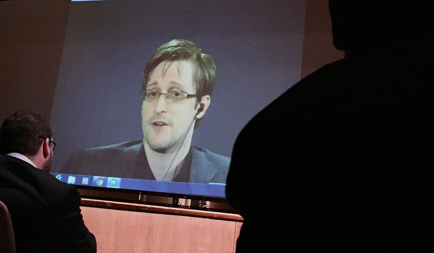 In this Feb. 17, 2016, file photo, former National Security Agency contractor Edward Snowden, center, speaks via video conference to people in the Johns Hopkins University auditorium in Baltimore. (AP Photo/Juliet Linderman, File)