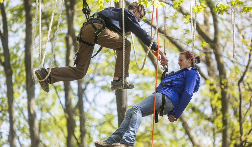 "In this photo taken Friday, May 13, 2016, Chloe Brouwer, a park staff member, is ""rescued"" during a safety drill at Treetop Adventure Park, a challenge ropes course, in Grand Rapids, Mich.. The course will open on May 20 and hold its grand opening celebration during Memorial Day Weekend. (Allison Farrand/The Grand Rapids Press via AP) ALL LOCAL TELEVISION OUT; LOCAL TELEVISION INTERNET OUT; MANDATORY CREDIT"