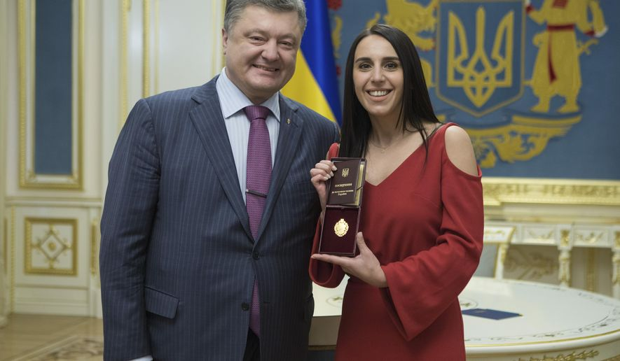 Ukraine's President Petro Poroshenko and Eurovision winner Jamala pose for a photograph after Poroshenko awarded the winner with a state award, in the Presidential Office in Kiev, Ukraine, Monday, May 16, 2016. Ukrainian singer Jamala's melancholic tune about Soviet dictator Josef Stalin's 1944 deportation of the Crimean Tatars, was crowned the winner of the 2016 Eurovision Song Contest early Sunday, an unusual choice for the kitschy pop fest. (Mykhailo Markiv/Pool Photo via AP)