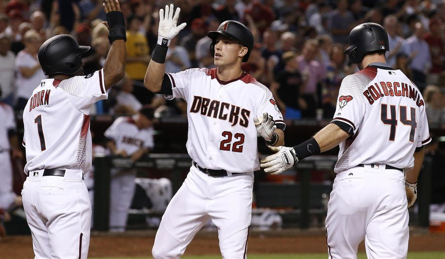 Arizona Diamondbacks' Jake Lamb (22) arrives at home plate to celebrate his three-run home run against the New York Yankees with Michael Bourn (1) and Paul Goldschmidt (44) during the fifth inning of a baseball game, Monday, May 16, 2016, in Phoenix. (AP Photo/Ross D. Franklin)