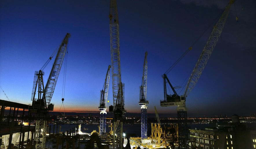 Cranes move loads of materials at dusk at the Hudson Yards construction site in New York on March 4, 2016. (Associated Press) **FILE**