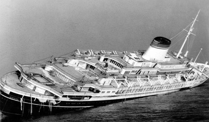 FILE - In this July 26, 1956 file photo, the Italian luxury liner Andrea Doria keels far over to starboard before sinking 225 feet to the bottom of the Atlantic 45 miles off Nantucket Island, Mass. Nearly six decades after the Andrea Doria slammed into another ocean liner, killing 46 people, explorers are preparing to do what 16 others have lost their lives attempting: get a fresh glimpse of the wreckage on the sea floor. Everett, Washington-based OceanGate will use a five-person submarine in June 2016 to get high-definition video and 3-D sonar images of the shipwreck.  (AP Photo/John Rooney, File)