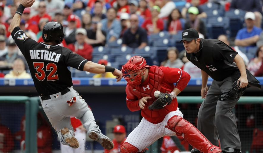 Miami Marlins' Derek Dietrich, left, scores past Philadelphia Phillies catcher Cameron Rupp, center, on a double by Christian Yelich during the first inning of a baseball game, Wednesday, May 18, 2016, in Philadelphia. Yelich advanced to third on the throw home. (AP Photo/Matt Slocum)