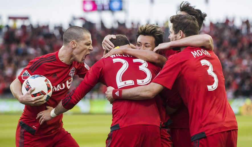 Toronto FC's Will Johnson, left, celebrates his goal with teammatesduring the first half of an MLS soccer game against New York City FC on Wednesday, may 18, 2016, in Toronto. (Mark Blinch/The Canadian Press via AP)