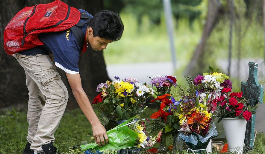 Christopher Martinez, 14, places flowers at a makeshift memorial Wednesday, May 18, 2016, for his classmate 11-year-old Josue Flores, who fatally stabbed while walking home from school the day before in Houston.  (Michael Ciaglo/Houston Chronicle via AP) MANDATORY CREDIT