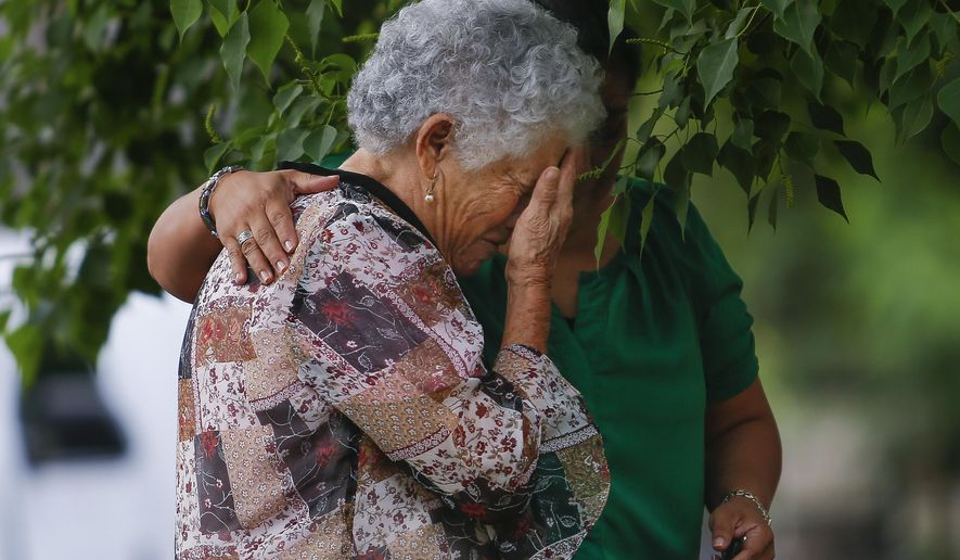 CORRECTS SPELLING OF GRANDMOTHER'S FIRST NAME TO ELISA INSTEAD OF LESA - Maria Cristina Sepulveda, right, comforts Elisa Mendes, the grandmother of 11-year-old Josue Flores, at a makeshift memorial for Flores, Wednesday, May 18, 2016, near where the youngster was fatally stabbed while walking home from school the day before in Houston. (Michael Ciaglo/Houston Chronicle via AP) MANDATORY CREDIT