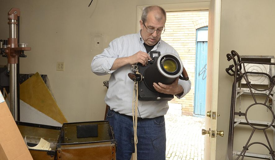 In a May 11, 2016 photo, Kevin Cooke, owner of Graule Studios in Rochester, holds a massive old camera used to take aerial photos, in Rochester, Pa. In 1892, Graule Studios opened its doors as a commercial photo business on Hinds Street in Rochester. The studio will shutter its doors this summer. (Lucy Schaly/Beaver County Times via AP) MANDATORY CREDIT