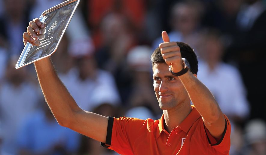 FILE - In this June 7, 2015, file photo, Serbia's Novak Djokovic shows his second place plate after losing to Switzerland's Stan Wawrinka in the final match of the French Open tennis tournament at the Roland Garros stadium in Paris. The French Open begins Sunday, May 22, 2016.  (AP Photo/Francois Mori, File)