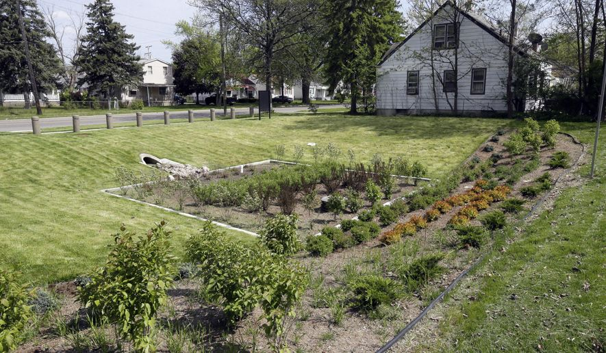 """In a Monday, May 16, 2016 photo ,  a """"bioretention garden"""" built to collect rain runoff from Evergreen Rd., is seen in the Warrendale neighborhood of Detroit.  A pilot project has transformed vacant lots into four gardens that are designed to capture and soak up storm water. Each garden is expected to achieve an average annual storm water volume reduction of 300,000 gallons and should help reduce street flooding during big storms. (AP Photo/Carlos Osorio)"""