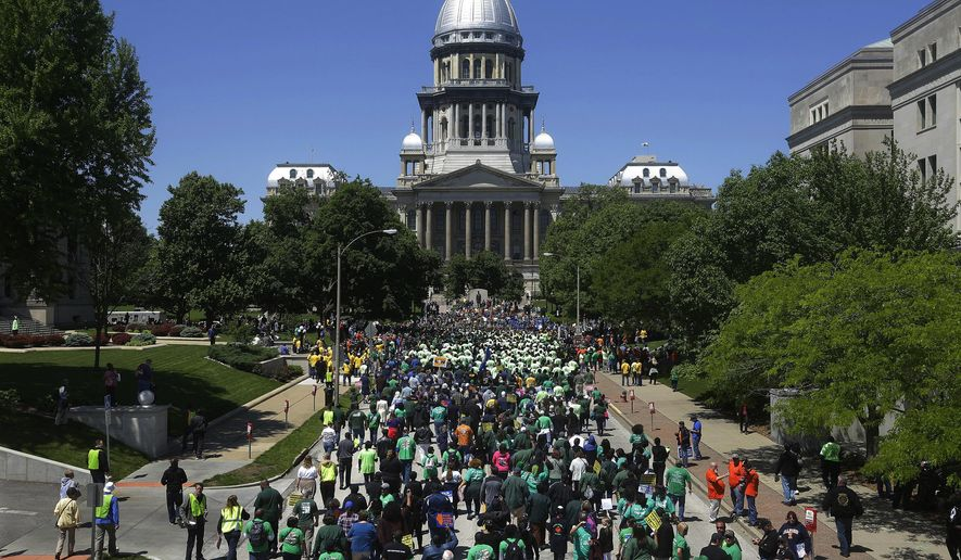Union supporters rally against Republican Illinois Gov. Bruce Rauner's calls to change collective bargaining policies, in front of the Illinois State Capitol Wednesday, May 18, 2016, in Springfield, Ill. The march is organized by a coalition of labor groups called Illinois Working Together. (AP Photo/Seth Perlman)