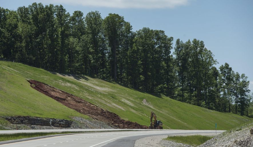In this May 13, 2016 photo, erosion has created a gash in the hillside along the new Interstate 69 section 4 near  Bloomington, Ind. Will Wingfield, Indiana Department of Transportation spokesman, said rain, combined with additional drainage from geological features in that area, caused the soil to slump. The area will be filled with rock to alleviate future problems. (Chris Howell/Bloomington Herald-Times via AP)